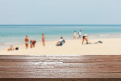 Wood table top on blurred blue sea and white sand beach with som. E people - Can be used for display or montage your products Stock Photo