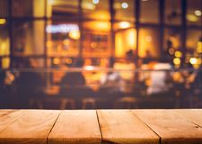 Wood table top on blurred of cafe restaurant with light gold. Wood table top on blurred of cafe  restaurant  with light gold in dark nigh background.For montage Stock Photo