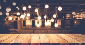 Wood table top on blurred of counter cafe shop with light bulb background. For montage product display or design key visual layout royalty free stock image