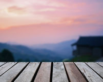 Wood table top on blurred home resort on mountain. At sunset Stock Image