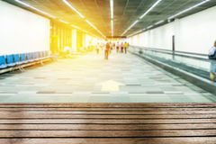 Wood table top on blurred passengers walking to gate Royalty Free Stock Photos