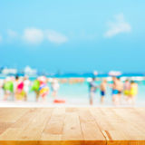 Wood table top with blurred people at the beach as background Stock Image
