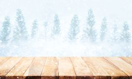 Wood table top on blurred snowfall in winter season background. Stock Images