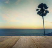 Wood table top on blurred sunset view with silhouette palm tree Royalty Free Stock Images