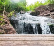 Wood table top on blurred waterfall flowing bright natural shini Royalty Free Stock Images