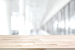 Wood table top on blurred white gray background of building hall Royalty Free Stock Photos