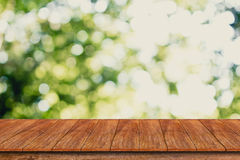 Wood table top on bokeh abstract green background Stock Photos