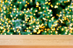 Wood table top with bokeh background from decorative light on christmas tree stock photo