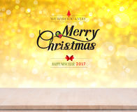 Wood table top on gold bokeh light. With Merry Christmas and Happy New Year 2017 text on background Stock Photos