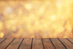 Wood table top on golden bokeh abstract background Royalty Free Stock Images