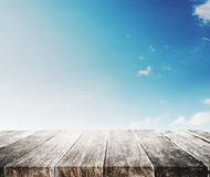 Wood table top on gradient blue sky and white clouds background Stock Images