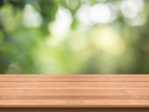Wood table top on nature green blurred background,for montage yo Royalty Free Stock Photo