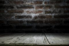Wood table top on old dark brick wall background. Empty wooden table for your product display montage on old dark brick wall background Stock Photos