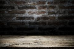 Wood table top on old dark brick wall background. Empty wooden table for your product display montage on old dark brick wall background Royalty Free Stock Photography