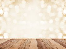 Wood table top over abstract golden background with white bokeh for Christmas and new year holidays. Montage style to display the
