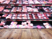 Wood table top over blur background of supermarket with meat pro. Duct shelf. Montage style to dispaly the product stock photos
