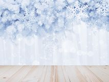 Wood table top over silver snowflakes shape and glitter on pine. Leaves with bokeh over white curtain background. Montage style to display the product stock photo