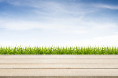 Wood table top panel, grass and sky background Royalty Free Stock Image