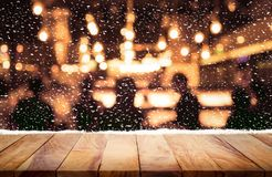 Wood table top with snowfall and people  in night winter background Stock Image