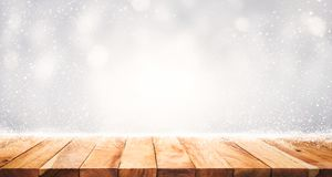 Wood table top with snowfall of winter season background. christmas stock photo
