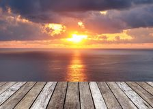 Wood table top on sunshine over sea in sunset. Wood table top on sunshine over sea at sunset Royalty Free Stock Photo
