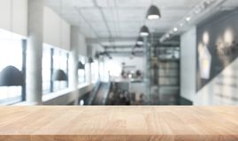 Wood table top texture on blur modern/contemporary building hall Stock Photography
