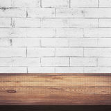 Wood table and white brick wall background texture Stock Photography