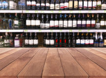 Wood table and wine Liquor bottle on shelf Blurred background Stock Images
