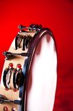 Wood Tambourine Red Closeup. A maple wood tambourine closeup  isolated on a red background in the vertical or portrait view with copy space Royalty Free Stock Image