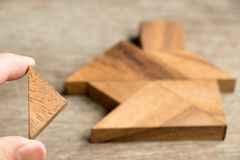 Wood tangram puzzle wait to fulfill in home shape. For build dream home , happy life , property investment, house loan concept stock images