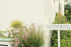 Wood tecken för bröllop mot den gröna suddighetsbakgrunden Träskylt med inskriften i vitt målarfärgbröllop Fotografering för Bildbyråer