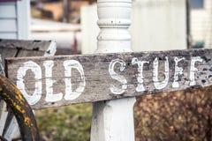 """Wood tecken för tappning""""OldStuff† på den vita Wood stolpen Royaltyfri Foto"""