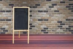 Wood tecken som placeras i rum med tegelstenväggen och trägolvet Arkivbild