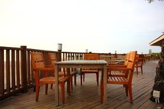 Wood terrace decorate with wood table and desk. Wood terrace with wooden table and desk on beach at sea view point.the restaurant on beach ,that there are wood stock photo