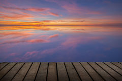 Wood terrace and the reflection of sunset. On sea water Royalty Free Stock Photos
