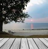 Wood terrass på stranden med stillsam plats, stort träd för kontur med strandstolar för att romantiska par ska koppla av på solne Royaltyfria Foton