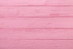 Wood texture or background of pastel pink color table. Pink texture of a wood table. Trendy pastel coloured background. Soft light, warm rose color stock photography