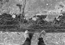 Male legs in sneakers, black and white. On concrete Stock Image