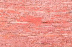 Wood texture with cracks in coral color. The rough wooden surface in the coral color royalty free stock photo