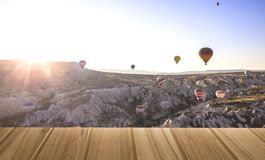 Wood top table on top View air balloons landing in a mountain Ca royalty free stock image