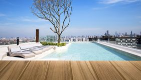 Wood top table on top View Beautiful Swimming pool in tropical r. Esort at summer day landscape view on top bangkok thailand,Can be used display or montage your royalty free stock photo