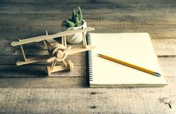Wood toy airplane with blank notebook and pencil on wood table . Stock Photography