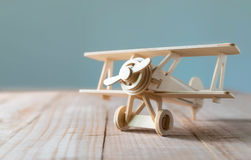 Wood toy airplane on wood table with blue clean background.  Royalty Free Stock Photo