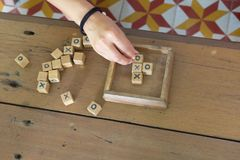 Wood toy is xo game. Wood toy is xo game, with hand player on wooden table background Stock Photo