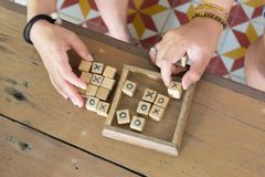 Wood toy is xo game. Wood toy is xo game, with hands players on wooden table background Stock Images
