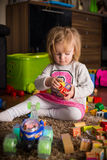 Wood toys. Girl 1-2 years old playing toy cubes in home on a floor Stock Images