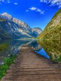 Wood trail into the water in the mountains. Germany, Bavaria, Berchtesgaden, Koenigssee - Beautiful walk and reflection of the mountains in the waters of the royalty free stock image