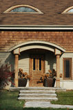 Wood Trim Home. Home with lots of wood trim and a wooden front door flanked by two planters royalty free stock images