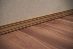 Wood Trim and Wood Flooring. View of wood trim along the wall with wood flooring stock image