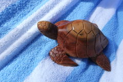 Wood Turtle Sculpture. A handmade wood turtle sculpture on beach towel Royalty Free Stock Photo